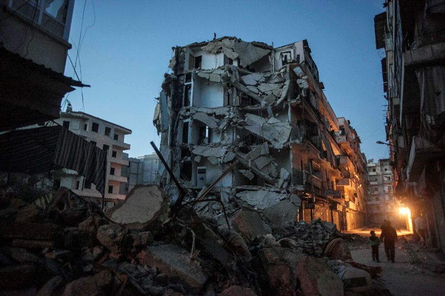 Residents walk past buildings damaged during heavy fighting between Free Syrian Army fighters and government forces in Aleppo, Syria, on Sunday, Dec. 2, 2012. (AP Photo/Narciso Contreras)