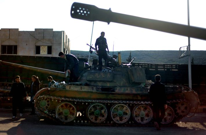 Syrian rebel fighters stand on a tank they took after storming a military base in Aleppo, Syria, on Monday, Nov. 19, 2012. (AP Photo/Khalil Hamra)