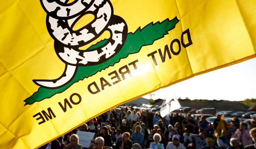 ** File ** A Don't Tread On Me flag flies over protesters during a rally at Leo O'Laughlin Inc. on the eve of President Obama's visit to Macon, Mo., on Tuesday, April 27, 2010. (AP Photo/Patrick T. Fallon)