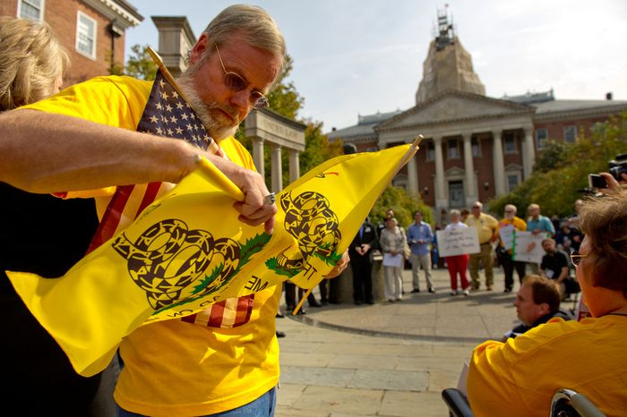 Jim Coyle of Hagerstown, Md., gets out an American flag and two Don't Tread on Me flags as he joins dozens of other Marylanders for a tea party rally in front of the Maryland Statehouse in Annapolis on Tuesday, Oct. 18,  2011. (Andrew Harnik/The Washington Times)