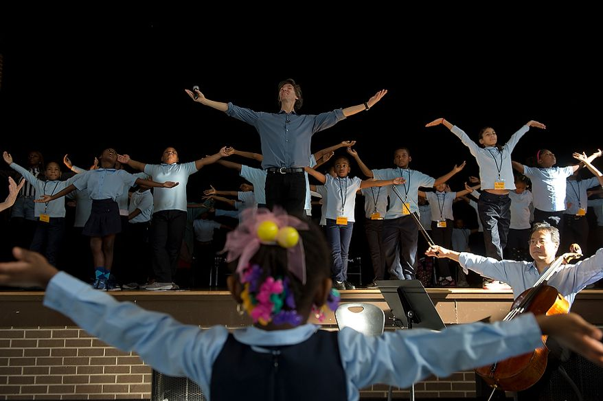 Damian Woetzel, center, a former principal dancer with the New York City Ballet, leads a group of Savoy Elementary School students, both on stage and in the audience, in a dance during a performance at the Southeast Washington, D.C. school on Tuesday, Dec. 4, 2012. Mr. Woetzel and world renowned cellist Yo Yo Ma came to the school to work with students in a small private workshop and then perform for the entire school. (Barbara L. Salisbury/The Washington Times)