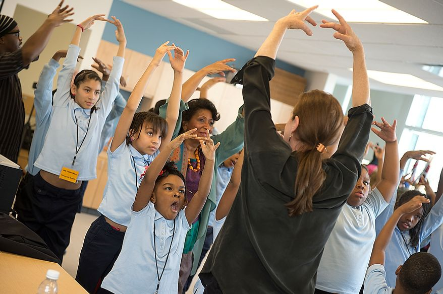 Savoy Elementary School student Anisa Nedab yawns as she and other students learn ballet positions with Heather Watts, center, a former ballerina with the New York City Ballet, during a special workshop at the school in Southeast Washington, D.C. on Tuesday, Dec. 4, 2012. (Barbara L. Salisbury/The Washington Times)