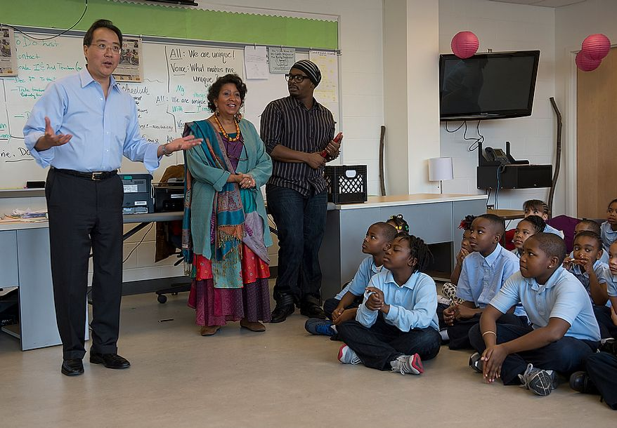 World renowned cellist Yo Yo Ma, left, greets students at Savoy Elementary School in Southeast Washington, D.C. before conducting a special workshop with former New York City Ballet principal dancer Damiam Woetzel on Tuesday, Dec. 4, 2012. The students and the artists then performed for the entire school. The artists were brought to the school as part of the Innovative Schedule for the Arts, a new program started up at the school only a couple of months ago that integrates the arts into students' everyday schedules. (Barbara L. Salisbury/The Washington Times)
