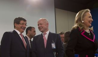 Turkish Foreign Minister Ahmet Davutoglu (left) speaks with British Foreign Minister William Hague (third from left) as U.S. Secretary of State Hillary Rodham Clinton stands at right during a meeting of NATO foreign ministers at the alliance's headquarters in Brussels on Tuesday, Dec. 4, 2012. (AP Photo/Virginia Mayo)