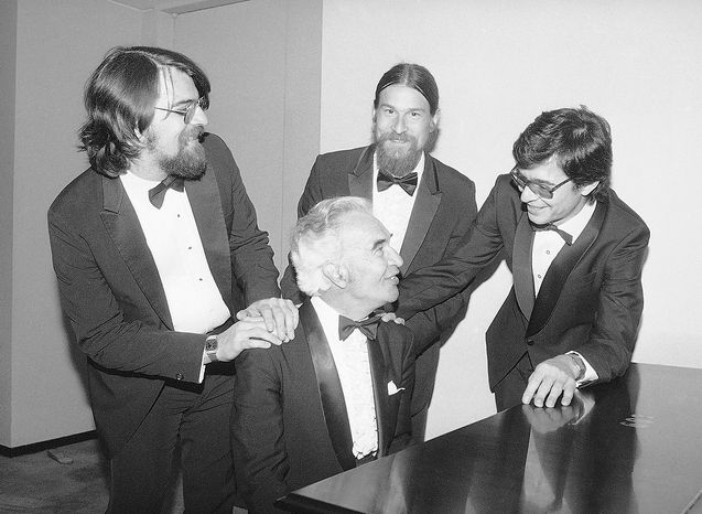 "A cheerful Dave Brubeck sits as his sons Chris, left, Danny and Darius, right, surround him during an intermission at Lincoln Center's Avery Fisher Hall, Saturday, June 23, 1985, New York. Joining Dave in his performance of ""The musical life of Dave Brubeck"", are his sons Chris on bass, Danny on the drums and Darius on the keyboards. (AP Photo/Richard Drew)"