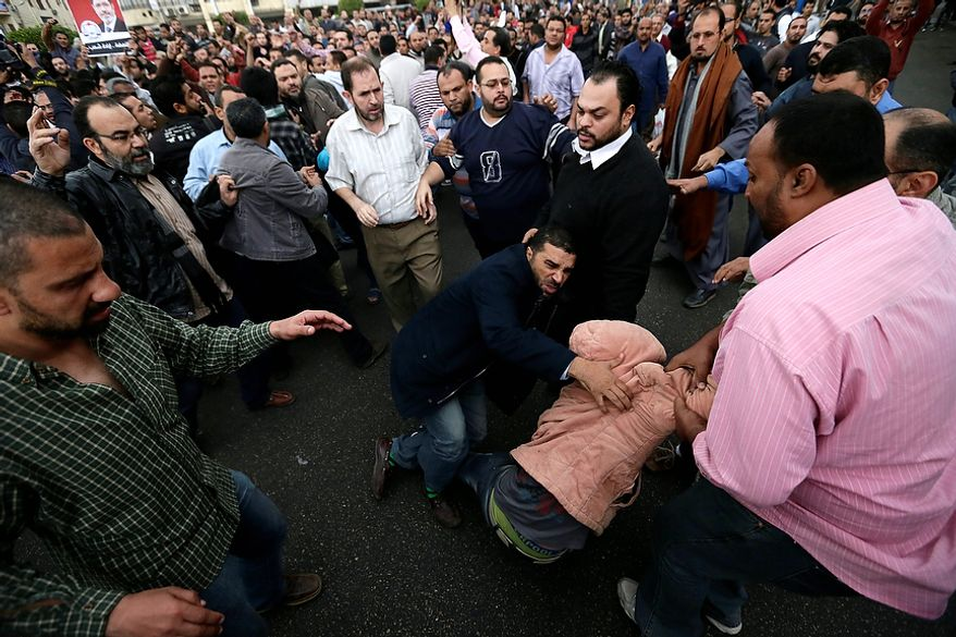 Egyptian President Mohammed Morsi's supporters try to detain an opposition protester during clashes outside the presidential palace, in Cairo, Egypt, Wednesday, Dec. 5, 2012. Wednesday's clashes began when thousands of Islamist supporters of Morsi descended on the area around the palace where some 300 of his opponents were staging a sit-in. (AP Photo/Hassan Ammar)