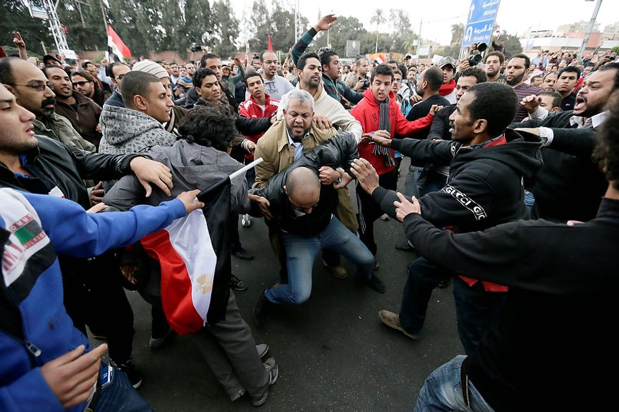 Egyptian President Mohammed Morsi's supporters beat an opponent, center, during clashes outside the presidential palace, in Cairo, Egypt, Wednesday, Dec. 5, 2012. Wednesday's clashes began when thousands of Islamist supporters of Morsi descended on the area around the palace where some 300 of his opponents were staging a sit-in. (AP Photo/Hassan Ammar)