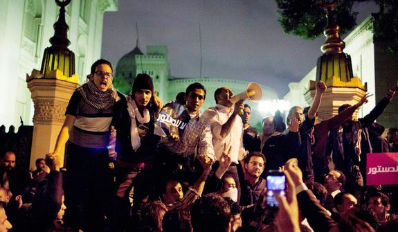 Egyptian protesters chant slogans against the Muslim Brotherhood during a rally Dec. 4, 2012, in front of the main gate of the presidential palace in Cairo. (Associated Press)