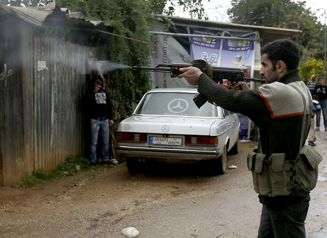 A Sunni gunman fires his weapon during clashes between pro- and anti-Syrian-regime gunmen in the port city of Tripoli, Lebanon, on Wednesday, Dec. 5, 2012. (AP Photo/Hussein Malla)