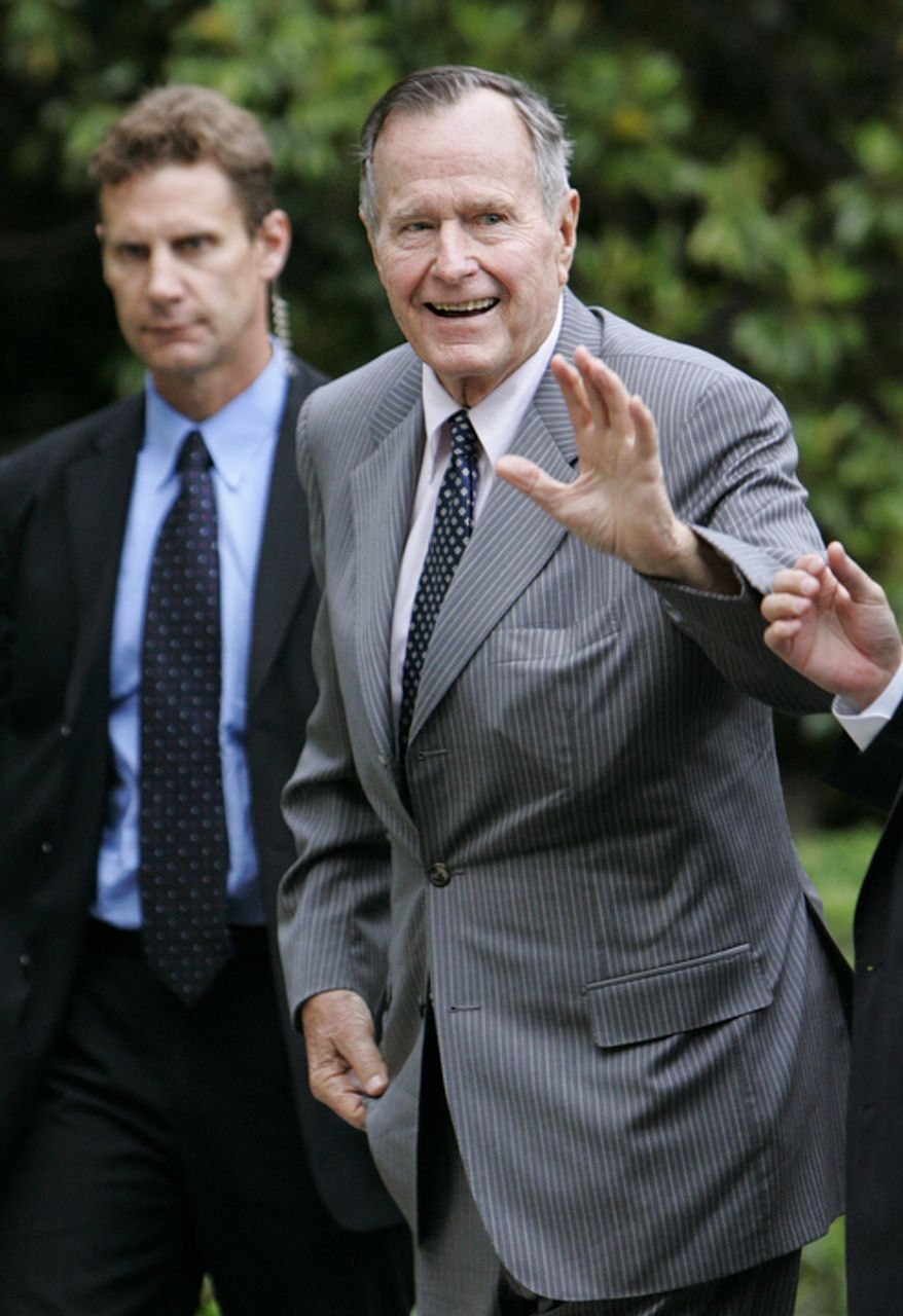 Former President George H.W. Bush waves as he arrives at the White House on Friday, May 19, 2006, in Washington. Mr. Bush was to speak at the commencement exercises at George Washington University on Sunday. The man on the left is an unidentified Secret Service agent. (AP Photo/Manuel Balce Ceneta)
