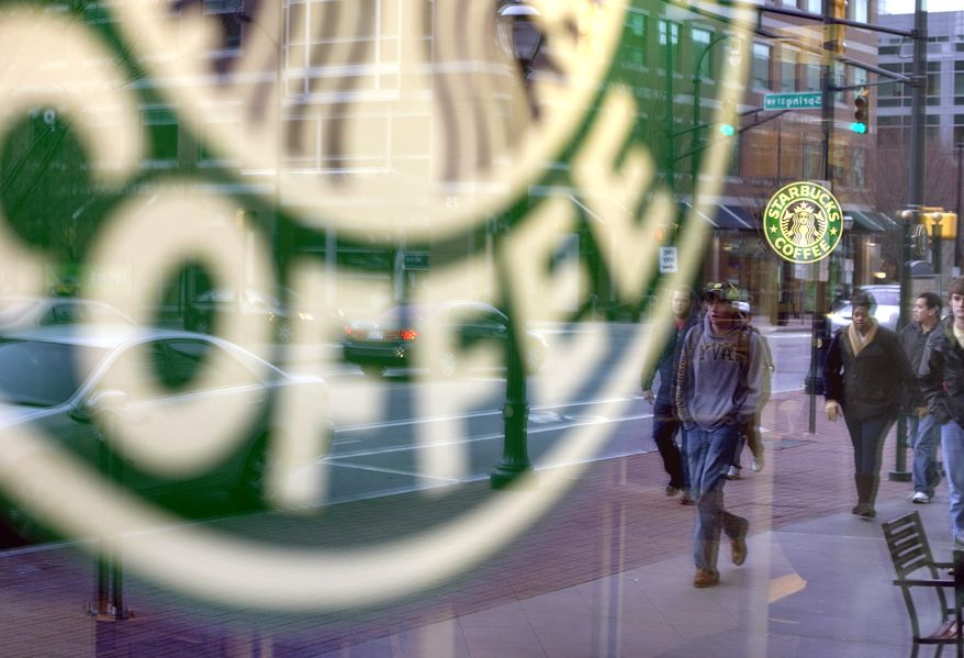 ** FILE ** Passing pedestrians are reflected in the window of a Starbucks store in Atlanta in January 2011. (AP Photo/David Goldman)