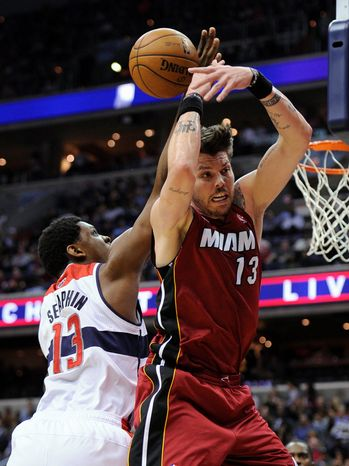 Washington Wizards forward Kevin Seraphin, left, of France, vies for the ball against Miami Heat forward Mike Miller during the first half of an NBA basketball game, Tuesday, Dec. 4, 2012, in Washington. The Wizards won 105-101. (AP Photo/Nick Wass)