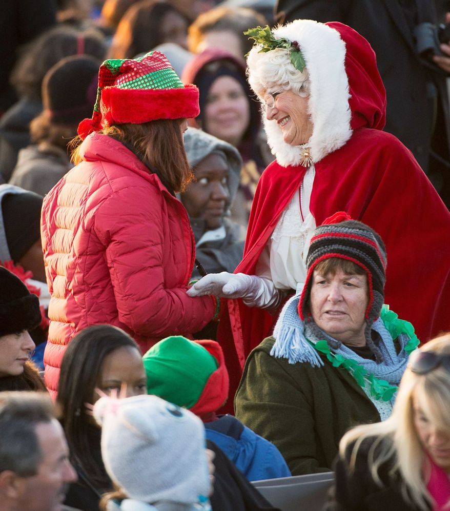 A festive crowd is bundled against a chilly evening Thursday for the annual lighting of the National Christmas Tree just south of the White House. (Andrew Harnik/The Washington Times)