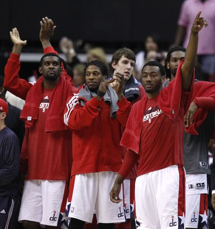 The Washington Wizards bench, from left, Chris Singleton, Cartier Martin, Jan Vesely, of the Czech Republic, John Wall, and Nene, of Brazil, clap as the final seconds run off the clock during the second half of an NBA basketball game against the Miami Heat on Thursday, April 26, 2012, in Washington. The Wizards defeated the Heat 104-70. (AP Photo/Evan Vucci)