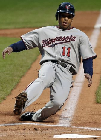 Minnesota Twins' Ben Revere (11) slides home to score form third on a sacrifice fly by Justin Morneau in the first inning of a baseball game against the Cleveland Indians, Tuesday, Sept. 18, 2012, in Cleveland. (AP Photo/Mark Duncan)