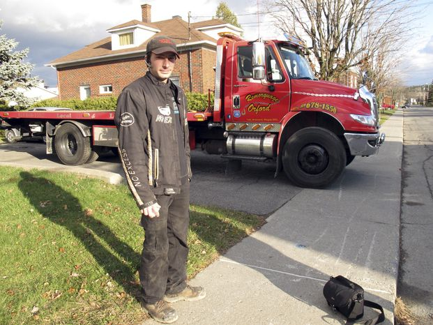 Nicholas Dostie stands Nov. 13, 2012, in front of his tow truck in Magog, Quebec, that he said he used to tow a van in which about a dozen men, women and children entered Canada illegally from the United States and applied for political asylum. Canadian immigration officials on Dec. 5, 2012 said a Romanian smuggling ring has been bringing Gypsies into the U.S. through Mexico in order for them to eventually gain asylum in Canada. (Associated Press)