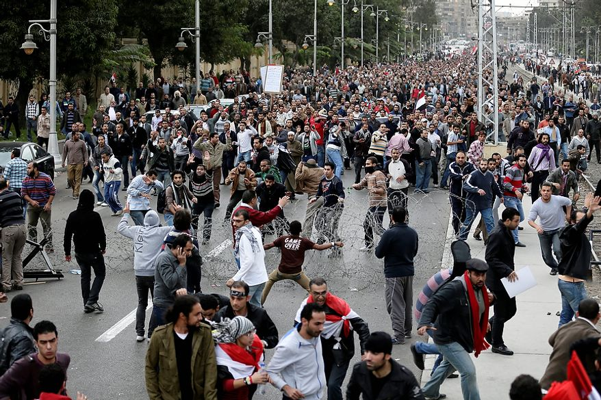 Supporters of Egyptian President Mohammed Morsi (background) clash with opponents (foreground) outside the presidential palace in Cairo on Dec. 5, 2012. The clashes began when thousands of Islamist supporters of Morsi descended on the area around the palace, where some 300 of his opponents were staging a sit-in. (Associated Press)