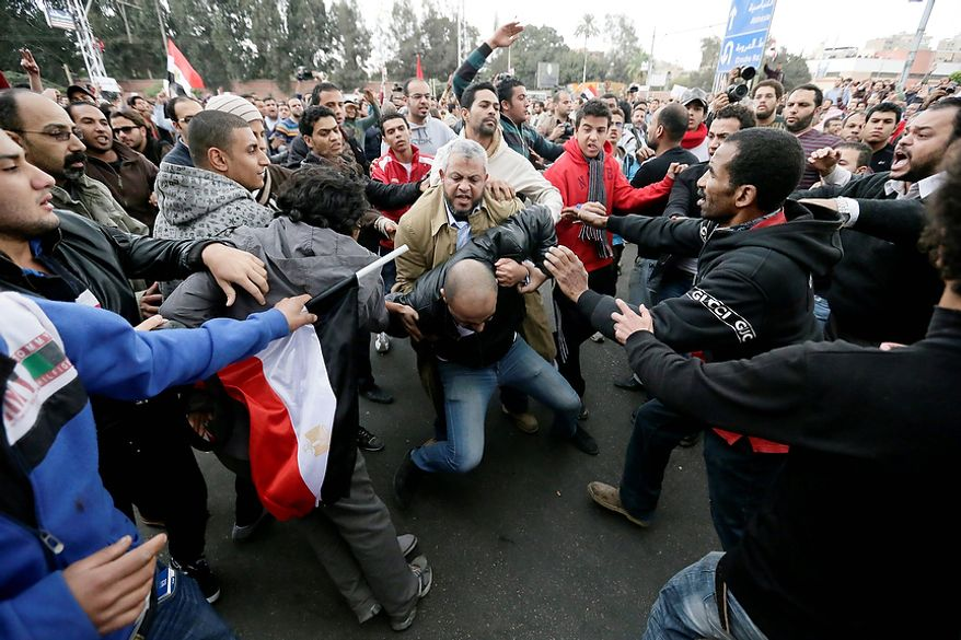 Supporters of Egyptian President Mohammed Morsi beat an opponent (center) during clashes outside the presidential palace in Cairo on Dec. 5, 2012. The clashes began when thousands of Islamist supporters of Morsi descended on the area around the palace where some 300 of his opponents were staging a sit-in. (Associated Press)