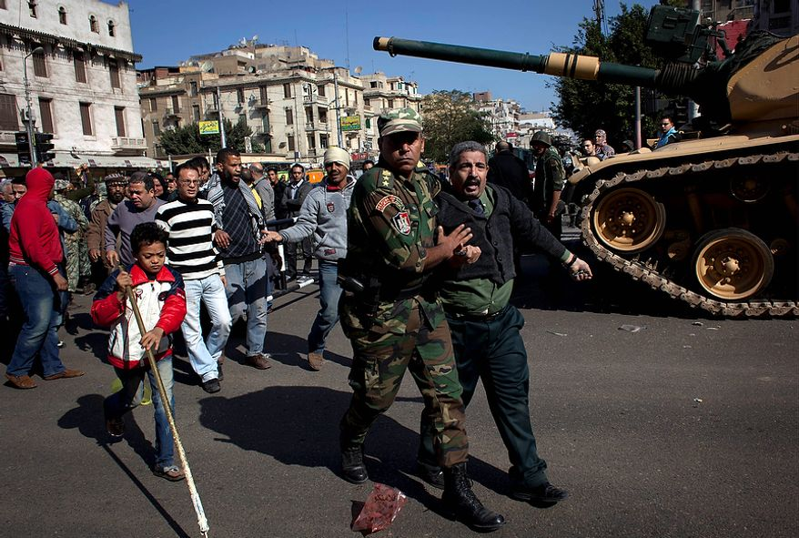 An Egyptian Army officer detains a man who was attacked by protesters gathering near the presidential palace in Cairo, while the army deploys to secure the site of overnight clashes between supporters and opponents of President Mohammed Morsi on Dec. 6, 2012. The Egyptian army has deployed tanks outside the presidential palace in Cairo following clashes between supporters and opponents of Morsi that left several people dead and hundreds wounded. (Associated Press)