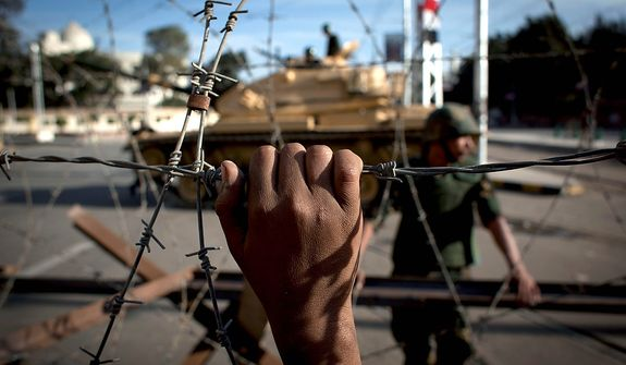 An Egyptian army tank securing the perimeter of the presidential palace in Cairo is seen behind barbed wire Dec. 6, 2012, while protesters on the other side chant slogans against President Mohammed Morsi. The Egyptian army deployed tanks and gave both supporters and opponents of Mohammed Morsi a deadline to leave the area outside the presidential palace following fierce street battles that left several people dead and hundreds injured. (Associated Press)