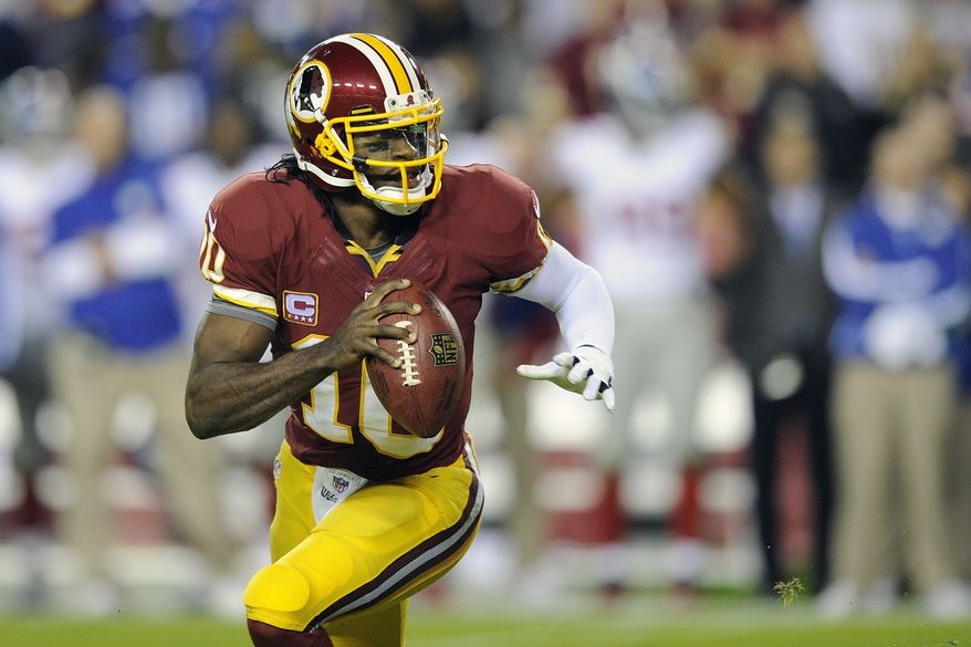 Washington Redskins quarterback Robert Griffin III scrambles with the ball during the first half of an NFL football game against the New York Giants in Landover, Md. Monday, Dec. 3, 2012. (AP Photo/Nick Wass)