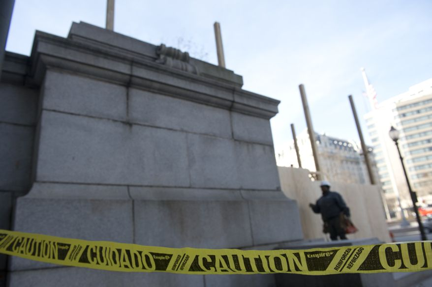 A construction worker stands inside the fenced off area outside the Wilson Building in Washington, D.C. on Thursday, Dec. 6, 2012. Work is underway to build a viewing platform here for the Inauguration parade. This Pennsylvania Avenue entrance is likely to be closed to the public through March so that the platform can be torn down after Jan. 21. (Barbara L. Salisbury/The Washington Times)