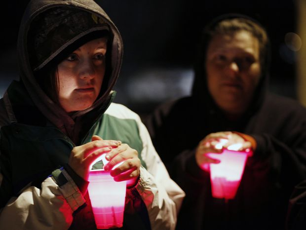 Amanda Smith holds a candle during a vigil held Dec. 5, 2012, at Meyers Lake in Evansdale, Iowa, for two young Iowa cousins who vanished five months ago while riding their bikes. (Associated Press/Waterloo Courier)