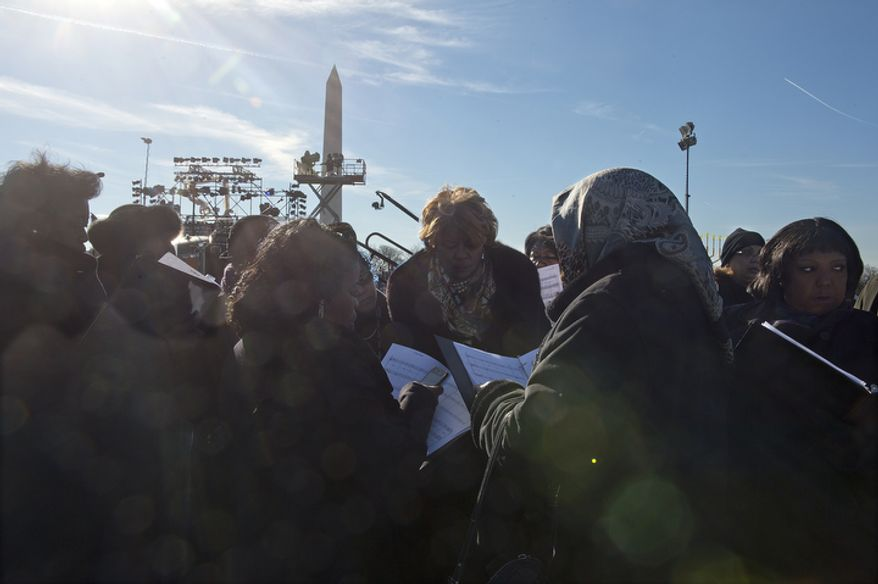 Members of the Washington Performing Arts Society gospel choir wait to take the stage Dec. 6, 2012, to rehearse for the lighting of the National Christmas tree on the Ellipse in downtown D.C. later that evening. (Barbara L. Salisbury/The Washington Times)