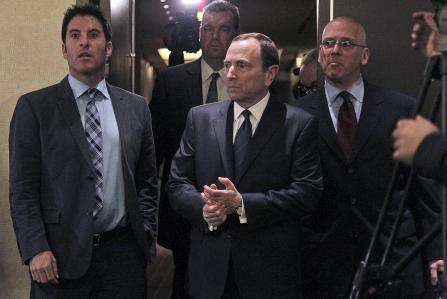 NHL commissioner Gary Bettman, center, arrives to speak with reporters after an NHL Board of Governors meeting, Wednesday, Dec. 5, 2012 in New York.  The NHL and NHL Players' Association have cleared their schedules with progress being made in collective bargaining talks. (AP Photo/Mary Altaffer)