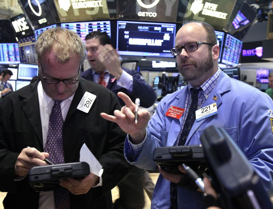 Traders Douglas Glander (left) and Peter Mancuso (right) work on the floor of the New York Stock Exchange on Thursday, Dec. 6, 2012. (AP Photo/Richard Drew)