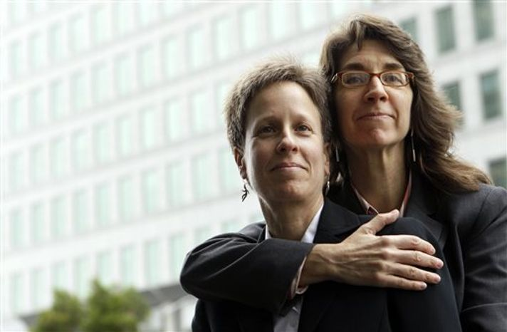 FILE - This Dec. 17, 2010 file photo shows Karen Golinski, right, hugging her wife Amy Cunninghis as they pose for a photograph outside of a federal court building in San Francisco. The fight over gay marriage is shifting from the ballot box to the Supreme Court. Three weeks after voters in three states backed it, the justices meet Friday