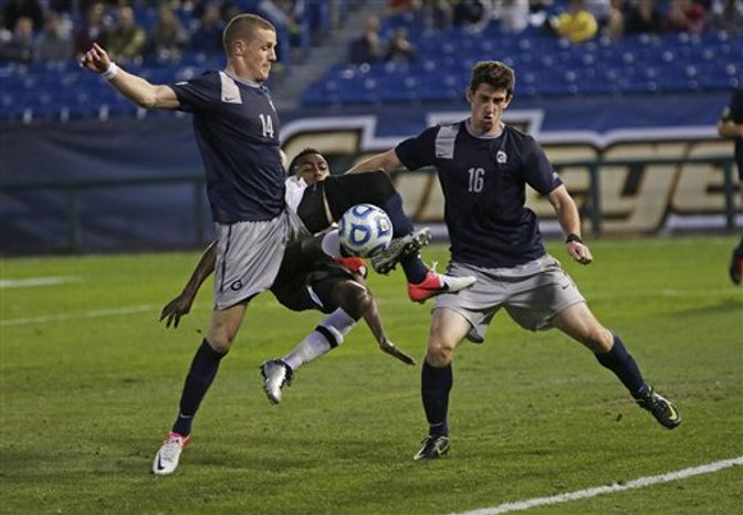 Maryland's Mikias Eticha, center, tries to shoot the ball between the defense of Georgetown's Cole Seiler, left, and Jimmy Nealis, right, in the second half of their NCAA College Cup men's championship semifinal soccer match at Regions Park, Friday, Dec. 7, 2012, in Hoover, Ala. Georgetown won in penalty kicks. (AP Photo/Dave Martin)