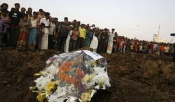 **FILE** Hundreds of Bangladeshi mourners watch Nov. 27, 2012, as the bodies of victims of a fire in a garment factory are buried in Dhaka, Bangladesh. The factory did not have any fire exits for its 1,400 workers, many of whom became trapped by the blaze. Investigators said the death toll would have been far lower if there had been even a single emergency exit. (Associated Press)