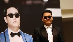 """South Korean rapper Psy, who gained popularity with his song """"Gangnam Style,"""" gives a press conference before a concert at the Marina Bay Sands in Singapore on Saturday, Dec. 1, 2012. (AP Photo/Wong Maye-E)"""