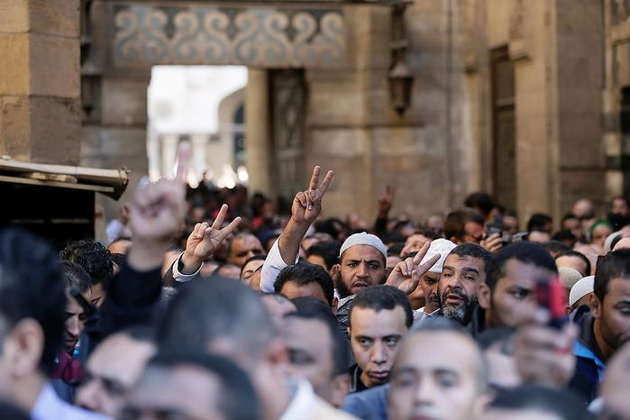 """Muslim Brotherhood and Egyptian President Morsi supporters chant slogans during a funeral of three victims who were killed during Wednesday's clashes outside Al-Azhar mosque, the highest Islamic Sunni institution, Friday, Dec. 7, 2012. During the funeral, thousands Islamist mourners chanted, """"with blood and soul, we redeem Islam,"""" pumping their fists in the air. """"Egypt is Islamic, it will not be secular, it will not be liberal,"""" they chanted as they walked in a funeral procession that filled streets around Al-Azhar mosque. Thousands of Egyptians took to the streets after Friday midday prayers in rival rallies and marches across Cairo, as the standoff deepened over what opponents call the Islamist president's power grab, raising the specter of more violence. (AP Photo/Hassan Ammar)"""