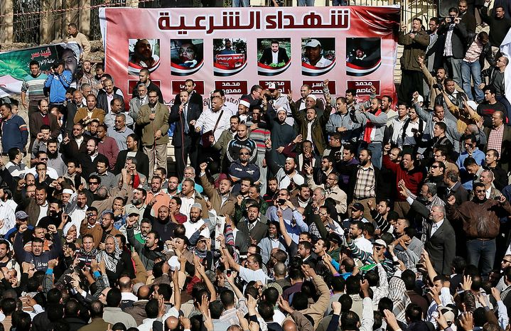 """Muslim Brotherhood and Egyptian President Morsi supporters chant slogans during the funeral of three victims who were killed during Wednesday's clashes outside Al-Azhar mosque, the highest Islamic Sunni institution, Friday, Dec. 7, 2012. During the funeral, thousands Islamist mourners chanted, """"with blood and soul, we redeem Islam,"""" pumping their fists in the air. """"Egypt is Islamic, it will not be secular, it will not be liberal,"""" they chanted as they walked in a funeral procession that filled streets around Al-Azhar mosque. Arabic on the poster, up, reads, """"Martyrs legitimacy."""" (AP Photo/Hassan Ammar)"""