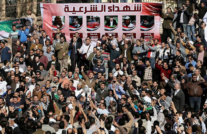 "Muslim Brotherhood and Egyptian President Morsi supporters chant slogans during the funeral of three victims who were killed during Wednesday's clashes outside Al-Azhar mosque, the highest Islamic Sunni institution, Friday, Dec. 7, 2012. During the funeral, thousands Islamist mourners chanted, ""with blood and soul, we redeem Islam,"" pumping their fists in the air. ""Egypt is Islamic, it will not be secular, it will not be liberal,"" they chanted as they walked in a funeral procession that filled streets around Al-Azhar mosque. Arabic on the poster, up, reads, ""Martyrs legitimacy."" (AP Photo/Hassan Ammar)"