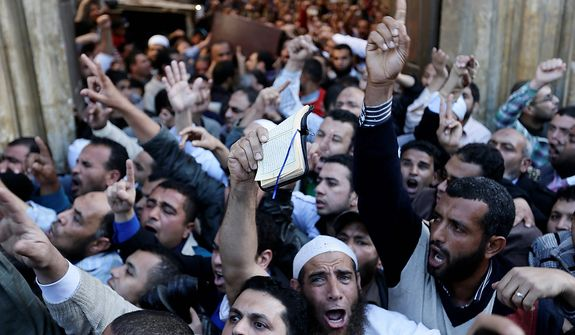 "Muslim Brotherhood and Egyptian President Morsi supporters chant slogans during a funeral of three victims who were killed during Wednesday's clashes outside Al Azhar mosque, the highest Islamic Sunni institution, Friday, Dec. 7, 2012. During the funeral, thousands Islamist mourners chanted, ""with blood and soul, we redeem Islam,"" pumping their fists in the air. ""Egypt is Islamic, it will not be secular, it will not be liberal,"" they chanted as they walked in a funeral procession that filled streets around Al-Azhar mosque. Thousands of Egyptians took to the streets after Friday midday prayers in rival rallies and marches across Cairo, as the standoff deepened over what opponents call the Islamist president's power grab, raising the specter of more violence. (AP Photo/Hassan Ammar)"
