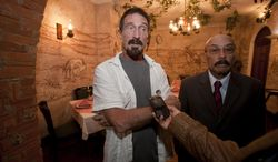 """**FILE** Software company founder John McAfee (left) accompanied by his lawyer, Telesforo Guerra, answers questions during an interview at a local restaurant in Guatemala City on Dec. 4, 2012. McAfee, 67, has been identified as a """"person of interest"""" in the killing of his neighbor in Belize, 52-year-old Gregory Faull. The anti-virus company founder fled Belize and is seeking political asylum in Guatemala, according to his lawyer. (Associated Press)"""