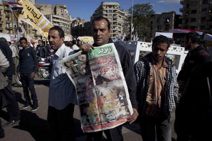 "An Egyptian protester carries a copy of Al Wafd newspaper front page that reads in Arabic, ""the brotherhood's crime, no legitimacy for a governor who is against his people,"" during a protest against President Mohammed Morsi near the presidential palace in Cairo on Dec. 7, 2012. (Associated Press)"