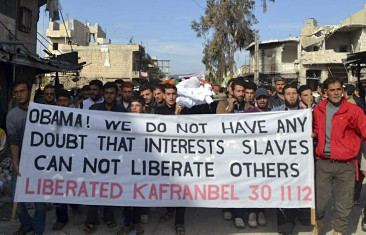 **FILE** This citizen journalism image provided by Edlib News Network (ENN), which has been authenticated based on its contents and other AP reporting, shows anti-Syrian regime protesters carrying a banner during a funeral of a man, who also carried by the protesters, at Kfar Nebel town, in the Idlib province of northern Syria on Nov. 30, 2012. The man was killed by the shelling of the Syrian forces loyal to Syrian President Bashar Assad. (Associated Press/Edlib News Network)