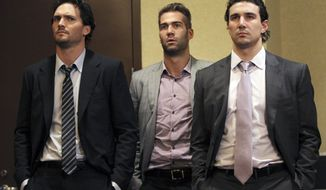 Winnipeg Jets' Ron Hainsey (left), Anaheim Ducks' Daniel Winnik (center), and Chicago Blackhawks' Chris Campoli listen as NHL Commissioner Gary Bettman and deputy commissioner Bill Daly speak to reporters in New York on Dec. 6, 2012. The NHL has rejected the players' latest offer for a labor deal, and negotiations have broken off at least until the weekend. (Associated Press)