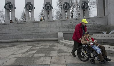 John Sekelsky of Croton-on-Hudson, N.Y. says he remembers he was ice skating on a big lake when the attack on Pearl Harbor occurred. He was in high school at the time but later enlisted in the Air Corps and served in England with the 487 Bomb Group. Here he gets a tour of the National World War II Memorial in Washington, D.C. with Dave Benbennick of the Honor Flight network before the National Pearl Harbor Remembrance Day ceremony on Friday, Dec. 7, 2012. (Barbara L. Salisbury/The Washington Times)
