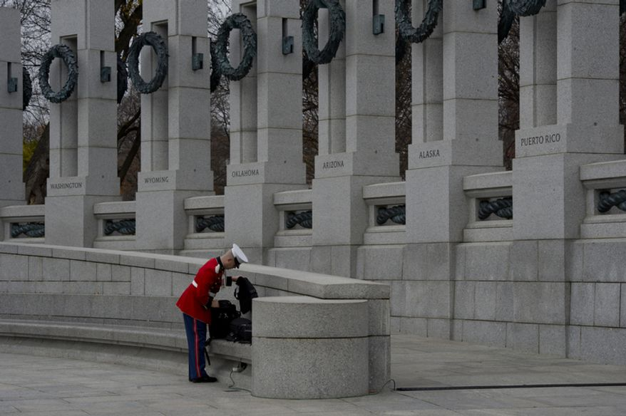 SSgt. Michael Warnick with the Marine Band brass quintet puts some gear on a bench at the National World War II Memorial in Washington, D.C. before performing at the National Pearl Harbor Remembrance Day ceremony Friday, Dec. 7, 2012. (Barbara L. Salisbury/The Washington Times)