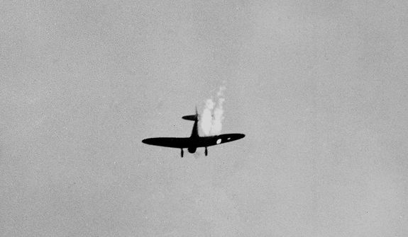A Japanese dive bomber goes into its last dive as it heads toward the ground in flames after it was hit by Naval anti-aircraft fire during surprise attack on Pearl Harbor, Dec. 7, 1941. (AP Photo)