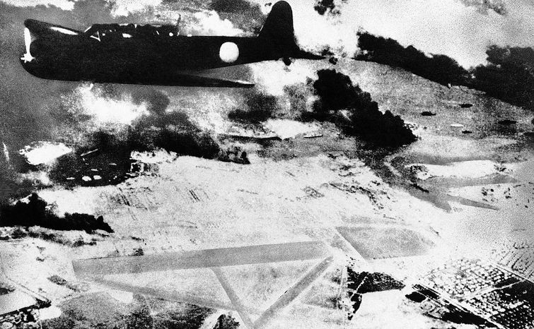 A Japanese bomber on a run over Pearl Harbor, Hawaii is shown during the surprise attack of Dec. 7, 1941. Black smoke rises from American ships in the harbor. Below is a U.S. Army air field.  (AP Photo)