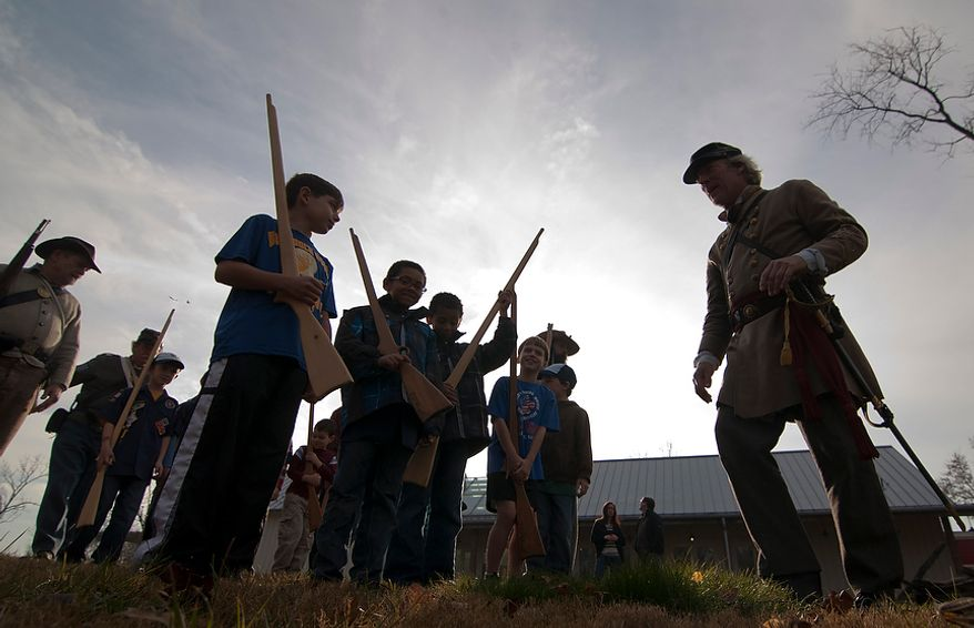 Chris Hoehne, 50, of Fairfax, Va., aligns Boy Scouts from Pack 15 in Fairfax while participants in a Civil War reenactment at Blenheim's Civil War Interpretive Center in Fairfax, Va., on Sunday, December 2, 2012. Hoehne is part of The Fairfax Rifles who partake in Civil War reenactment though out the year. (Craig Bisacre/The Washington Times)