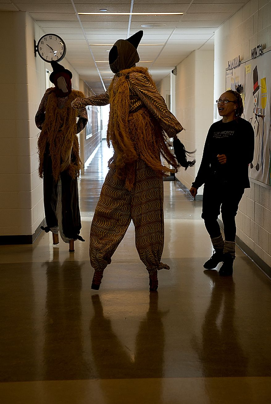 Bonita Cacho, right, who works with the arts intensive after-school program at Savoy Elementary School in Southeast Washington, D.C., works with two students dressed as Allegaries, or spiritual protectors of the village, to practice their stilt walking in the school's hallway on Tuesday, Dec. 4, 2012. (Barbara L. Salisbury/The Washington Times)