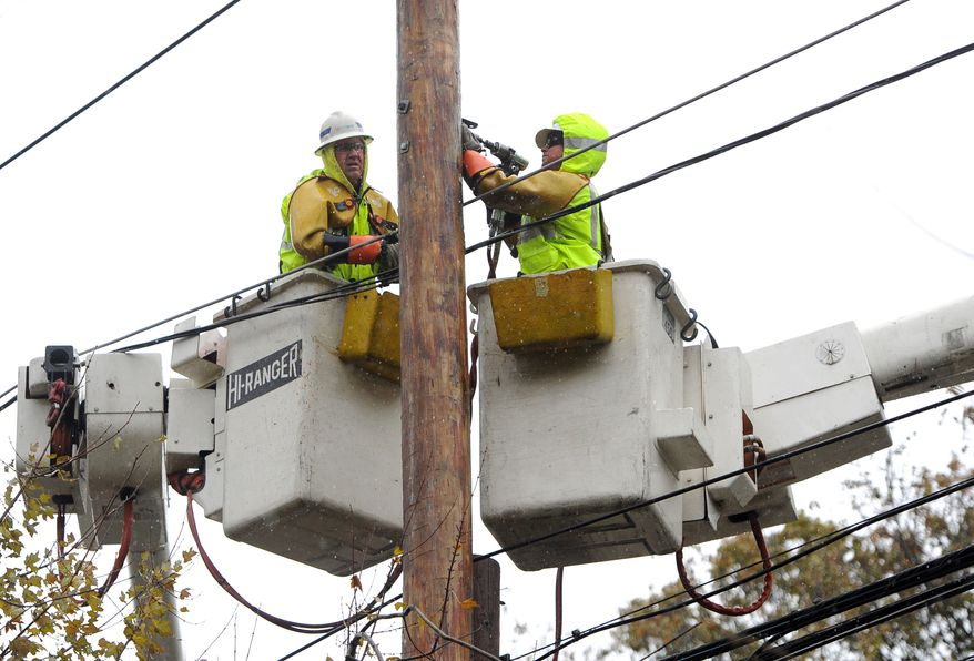 **FILE** A National Grid crew from Fredonia, N.Y., repair power lines that were brought down from the effects of Superstorm Sandy on Port Washington Blvd. in Port Washington, N.Y., on Nov. 7, 2012. (Associated Press)