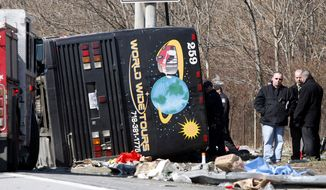 **FILE** Emergency personnel investigate the scene of a bus crash on Interstate 95 in the Bronx borough of New York on March 12, 2011. The bus driver, Ophadell Williams, who was charged in the crash that killed 15 passengers, said a tractor-trailer cut him off and he lost control. The bus carrying gamblers coming from a Connecticut casino was sheared open like a sardine can when it struck a pole. (Associated Press)